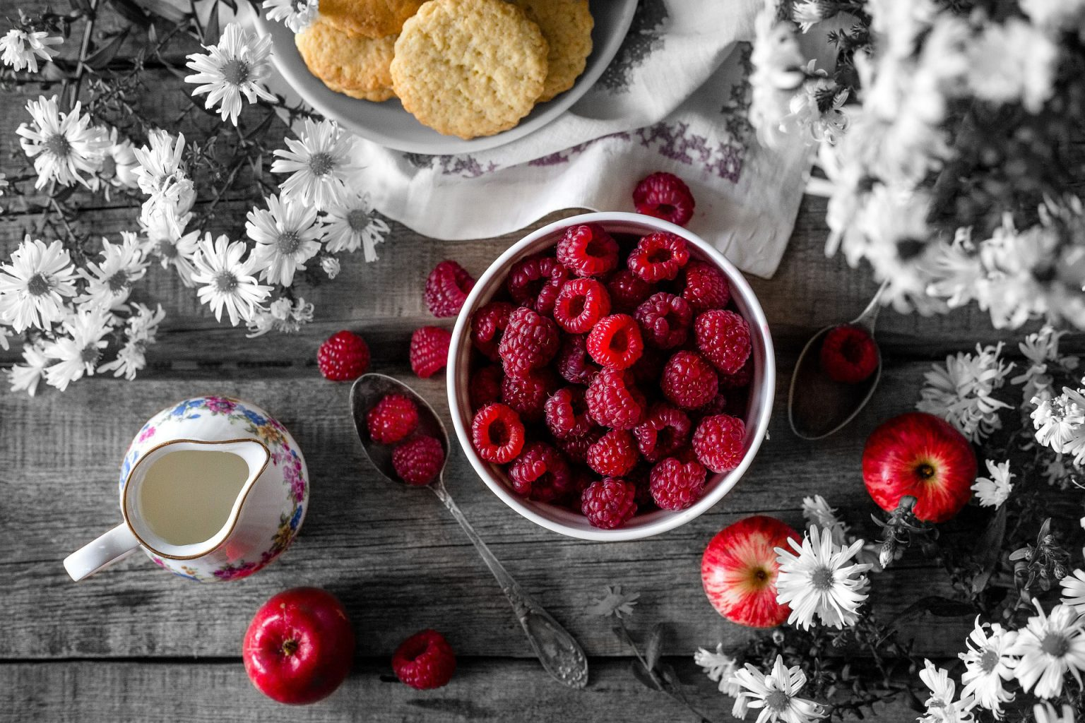 On the table Some berries, few apples and snacks are placed