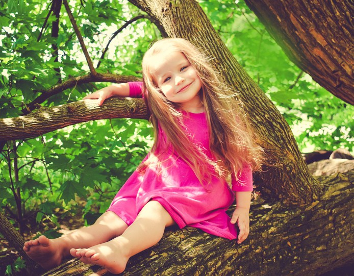 A little girl is sitting on the branch
